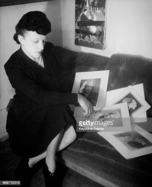 MichelMarie Poulain regardant ses portraits à Paris France circa 1940