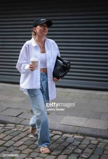 Michi Brandl wearing Agolde blue jeans, brown Balenciaga slides, white Zara crop top, white Karo Kauer Label blouse, black Bottega Veneta bag and...