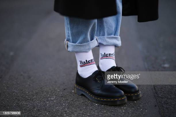 Michi Brandl wearing black Zara coat, Levis blue jeans, white Balenciaga socks and black Dr Martens shoes on March 25, 2021 in Cologne, Germany.