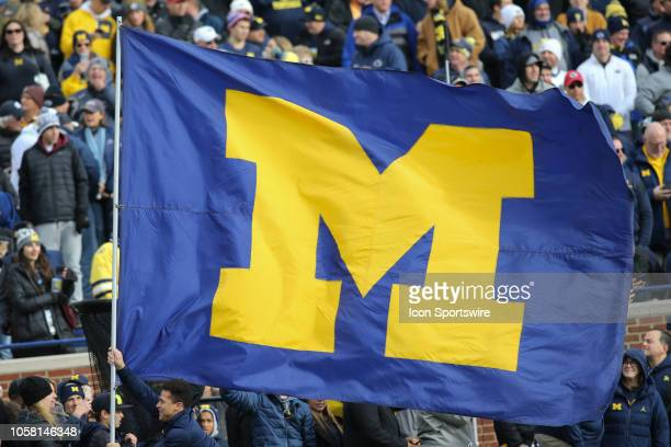 Michigan cheerleader runs across the field with the Michigan flag before the start of a game between the Penn State Nittany Lions and the Michigan...