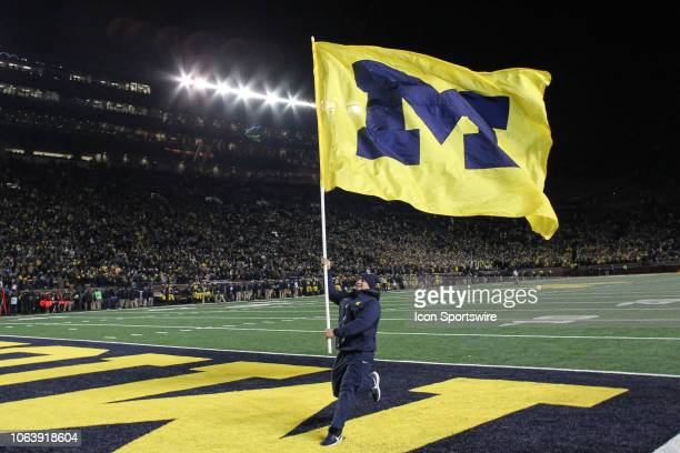 Michigan cheerleader runs with a Michigan flag after a score during a game between the Indiana Hoosiers and the Michigan Wolverines on November 17...