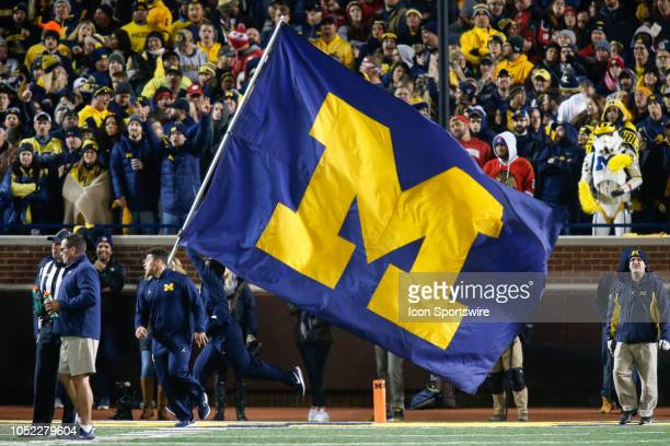 Michigan cheerleader runs with the Michigan flag across the field after a score during a game between the Wisconsin Badgers and the Michigan...