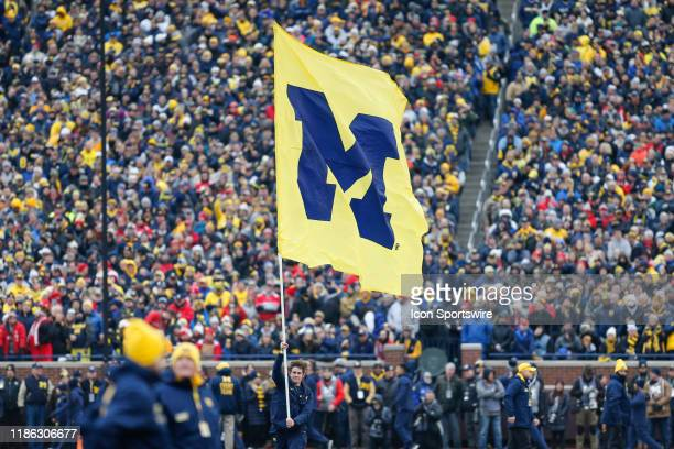 Michigan cheerleader runs with the Michigan logo flag after a score during a regular season Big 10 Conference game between the Ohio State Buckeyes...