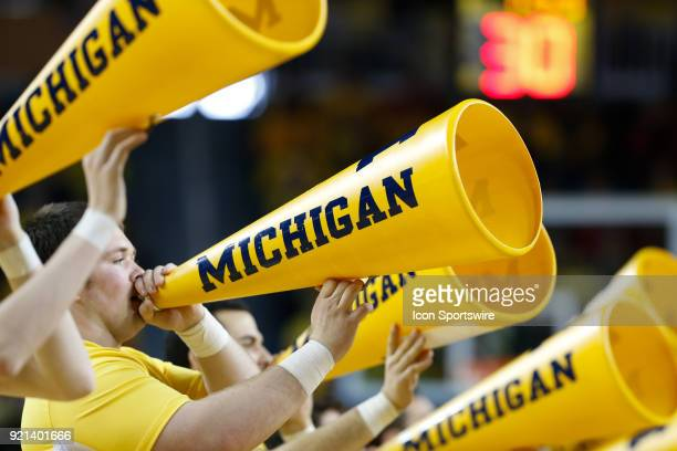 Michigan cheerleaders cheer with their megaphones during a timeout during a regular season Big 10 Conference basketball game between the Ohio State...