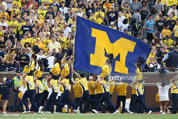 Michigan Cheerleaders lead a cheer during the game against the Minnesota Golden Gophers at Michigan Stadium on October 5 2013 in Ann Arbor Michigan...