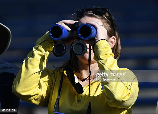 Michigan fan uses a pair of binoculars to get a better view of the Wolverines while they were warming up before taking on Maryland on November 11...