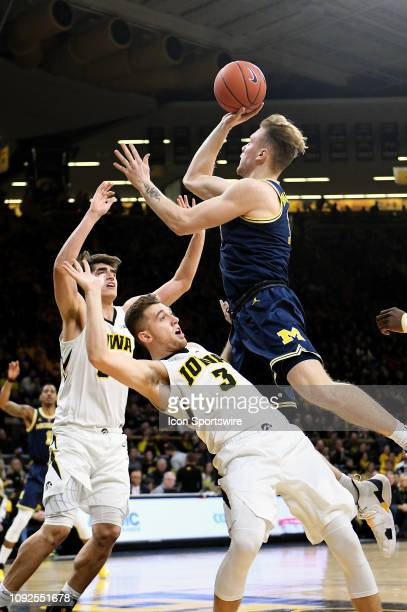 Michigan forward Ignas Brazdeikis drives in to Iowa Hawkeyes guard Jordan Bohannon during a Big Ten Conference basketball game between the Michigan...