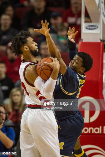 Michigan guard Zavier Simpson tries to get the ball away from Nebraska forward Isaac Copeland during the first half of a college basketball game...
