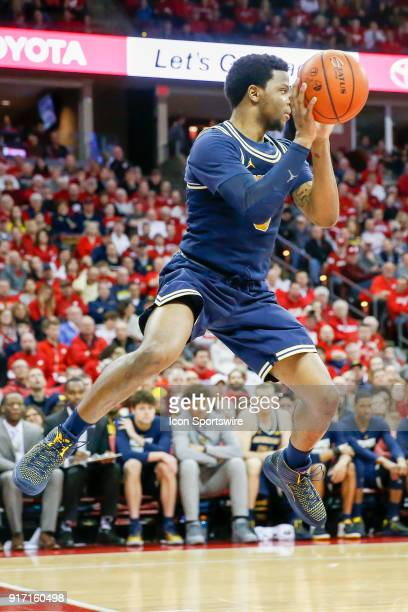 Michigan guard Zavier Simpson tries to keep the ball in bounds during a college basketball game between the University of Wisconsin Badgers and the...