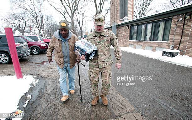 Michigan National Guard Staff Sergeant Steve Kiger of Beaverton Michigan helps a Flint Michigan resident take bottled water out to his car after he...