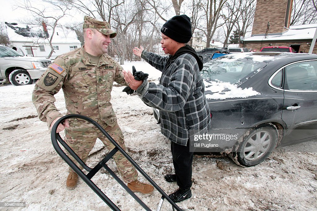 Michigan National Guard Staff Sergeant Steve Kiger of Beaverton, Michigan, gets a hug from Christine Brown of Flint, Michigan after he helped her take bottled water out to her car after she received it at a Flint Fire Station January 13, 2016 in Flint, Michigan. On Tuesday, Michigan Gov. Rick Snyder activated the National Guard to help the American Red Cross distribute water to Flint residents to help them deal with the lead contamination that is in the City of Flint's water supply.