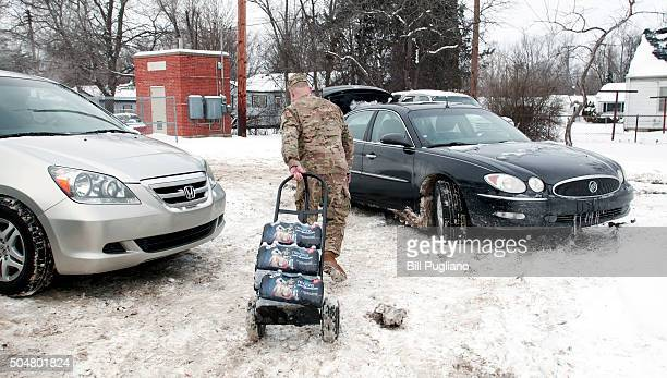 Michigan National Guard Staff Sergeant Steve Kiger of Beaverton Michigan helps Christine Brown of Flint Michigan take bottled water out to her car...