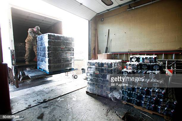 Michigan National Guard Staff Sergeant William Phillips of Birch Run Michigan helps unload pallets of bottled water at a Flint Fire Station January...