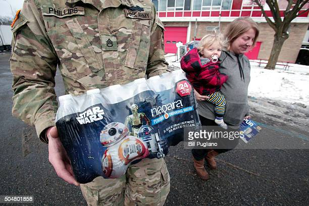 Michigan National Guard Staff Sergeant William Phillips of Birch Run Michigan helps Flint resident Amanda Roark and her son Dash take bottled water...