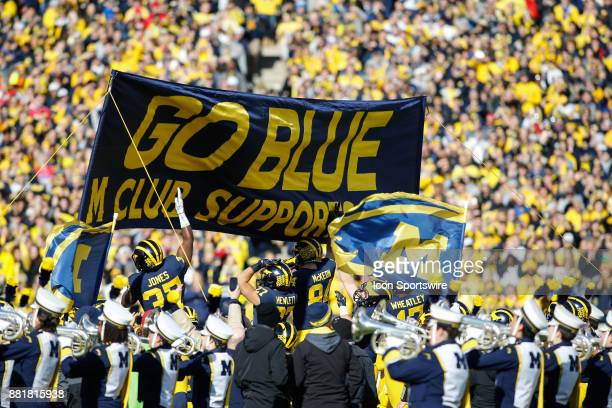 Michigan players jump up to touch the M Club banner as they run onto the field prior to the start of the game between the Ohio State Buckeyes and the...