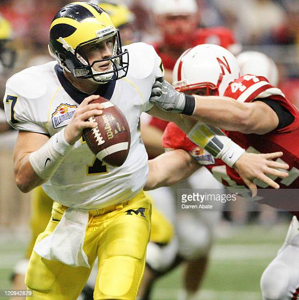 Michigan quarterback Chad Henne evades Nebraska's Jay Moore during the 2005 MasterCard Alamo Bowl game game between the University of Michigan...