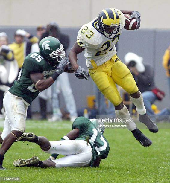 Michigan running back Chris Perry runs with the ball as two Michigan State Spartans try to bring him down Saturday against the Spartans of Michigan...
