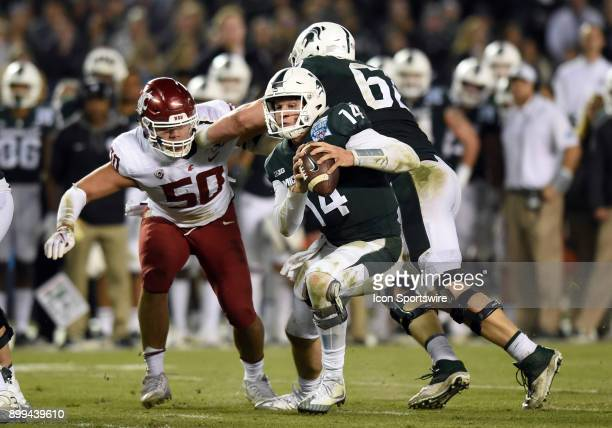 Michigan State Brian Lewerke escapes the grasp of Michigan State Sean Harrington during the Holiday Bowl game between the Washington State Cougars...