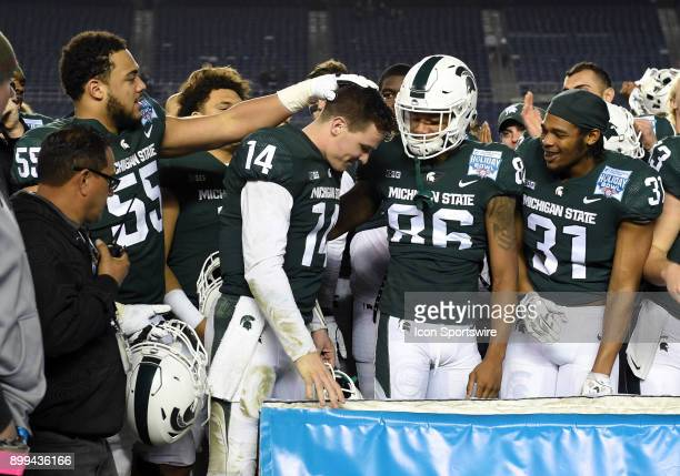 Michigan State Brian Lewerke is congratulated by his team mates after being named the offensive player of the game during the Holiday Bowl game...