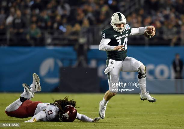 Michigan State Brian Lewerke leaps and escapes the grasp of Washington State Jahad Woods during the Holiday Bowl game between the Washington State...