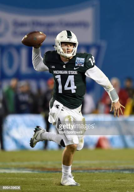 Michigan State Brian Lewerke rolls out of the pocket to attempt a pass during the Holiday Bowl game between the Washington State Cougars and the...