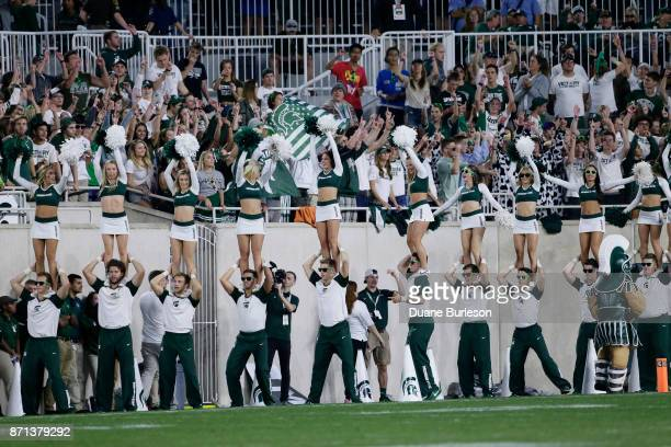 Michigan State cheerleaders and fans cheer their team during the second half of a game against the Indiana Hoosiers at Spartan Stadium on October 21...