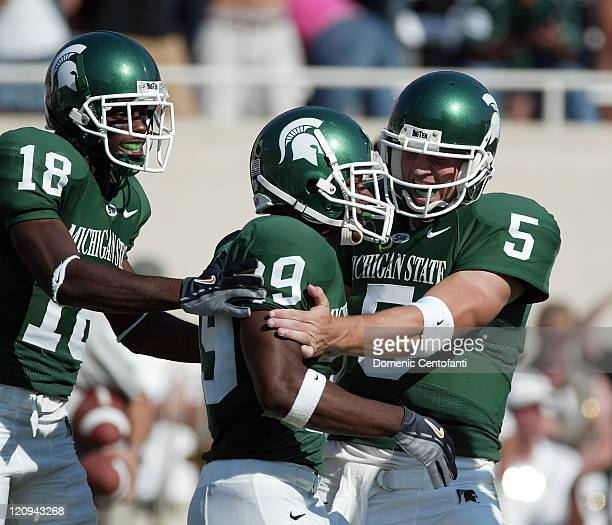 Michigan State freshman Javon Ringer gets congratulated by quarterback Drew Stanton and wide receiver Terry Love after Ringer scored a touchdown to...