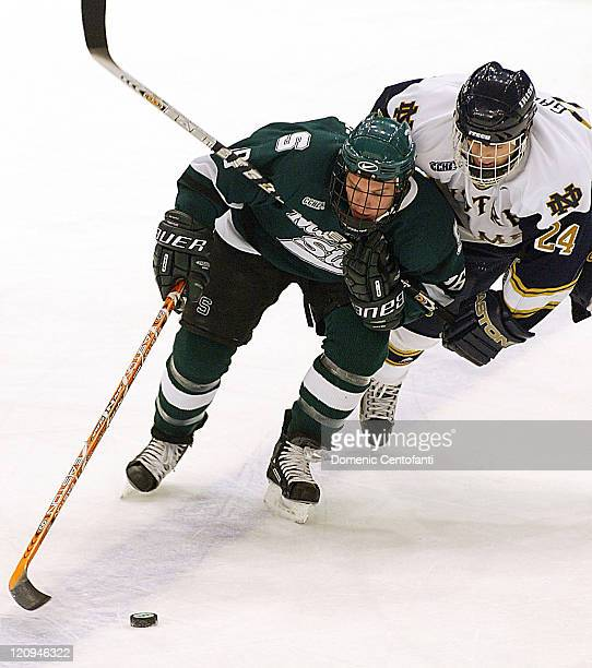 Michigan State freshman left wing Tyler Howells and Notre Dame senior defensmen Tom Galvin go after the puck The two teams tied 33 after OT