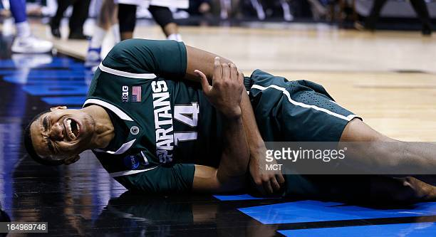 Michigan State guard Gary Harris grimaces in pain after falling hard in second half action in their NCAA fourth round game on Friday, March 29 in...
