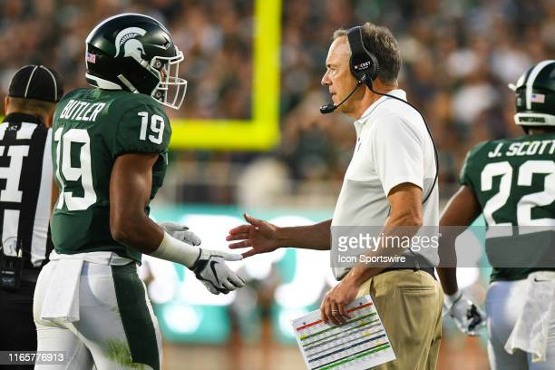Michigan State head coach Mark Dantonio greets cornerback Josh Butler after Butler forces a defensive safety during a college football game between...