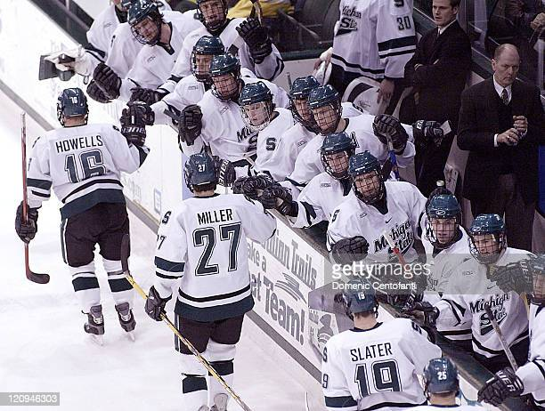 Michigan State players on the bench congratulate the line that was on the ice after State scored a goal in the second period during a game against...