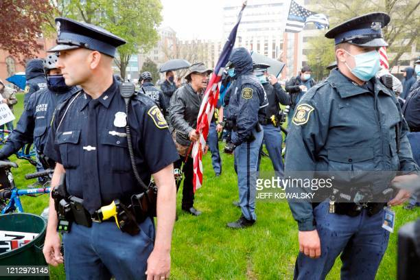TOPSHOT Michigan State Police patrol as demonstrators protest in Lansing Michigan during a rally organized by Michigan United for Liberty on May 14...
