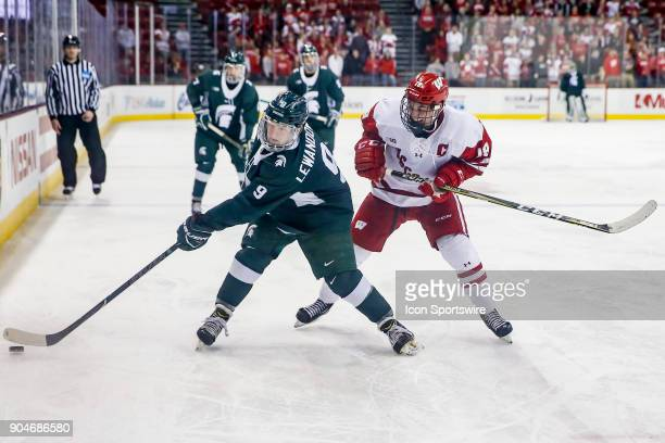 Michigan State right wing Mitchell Lewandowski stick handles the puck while Wisconsin left wing Cameron Hughes prepares to apply a check during a...