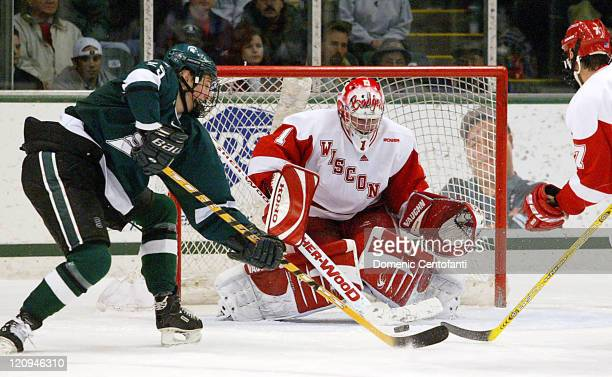 Michigan State Spartan Brock Radunske gets some wood on this backhand shot against Wisconsin goalie Brian Elliot in overtime to no avail The Michigan...