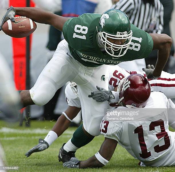 Michigan State Spartan tight end Jason Randall tries to break free from Indiana's Leonard Bryant and Josh Moore after a completion during the first...