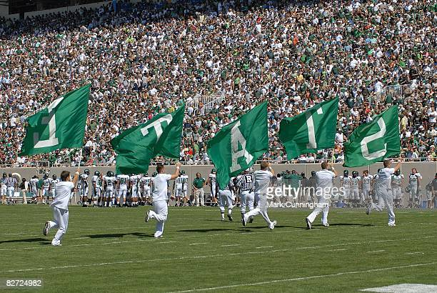 Michigan State Spartans cheerleaders run on the field with flags after a score against the Eastern Michigan Eagles on September 6 2008 at Spartan...