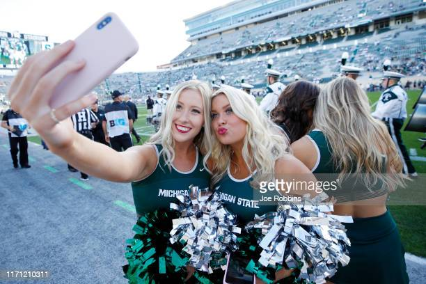 Michigan State Spartans cheerleaders take photos on the sideline prior to a game against the Tulsa Golden Hurricane at Spartan Stadium on August 30...