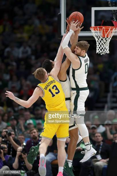 Michigan State Spartans forward Kyle Ahrens and Michigan Wolverines forward Ignas Brazdeikis battle for a rebound during a Big Ten Tournament...