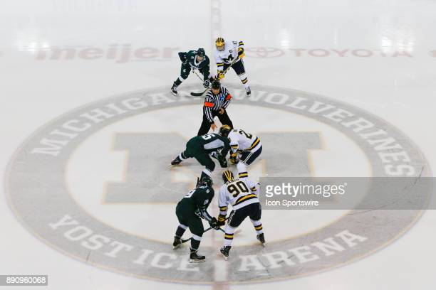 Michigan State Spartans forward Patrick Khodorenko and Michigan Wolverines forward Cooper Marody battle for control of the puck during a faceoff to...