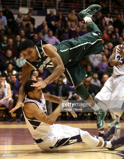 Michigan State Spartans guard Gary Harris commits an offensive foul while running into Northwestern Wildcats guard/forward Sanjay Lumpkin during the...