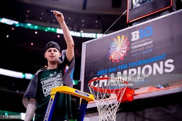 Michigan State Spartans guard Matt McQuaid holds a piece of the net up after the Big Ten Tournament championship game between the Michigan State...