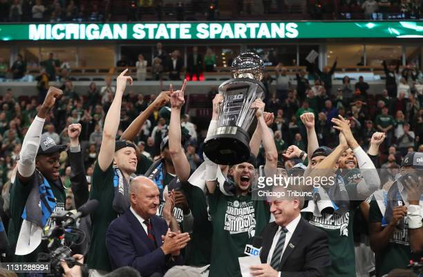 Michigan State Spartans guard Matt McQuaid holds the trophy as they celebrate their win Sunday March 17 2019 in the Big Ten tournament championship...