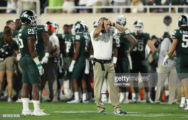 Michigan State Spartans head football coach Mark Dantonio watches the replay after a second quarter fumble in the end zone during the game against...