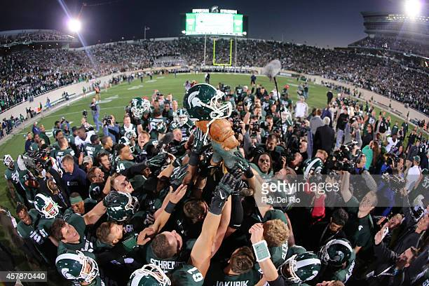 Michigan State Spartans lift the Paul Bunyan trophy after the game against the Michigan Wolverines at Spartan Stadium on October 25 2014 in East...
