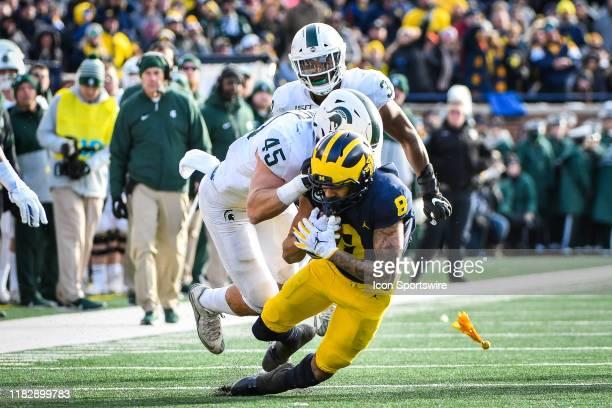 Michigan State Spartans linebacker Noah Harvey tackles Michigan Wolverines wide receiver Ronnie Bell during the Michigan Wolverines versus Michigan...