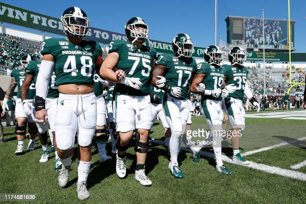 Michigan State Spartans players walk around the field with locked arms prior to the game against the Arizona State Sun Devils at Spartan Stadium on...
