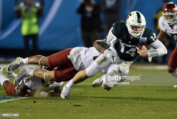 Michigan State Spartans quarterback Brian Lewerke is tackled from behind after gaining yards on a scramble by Washington State Cougars linebacker...