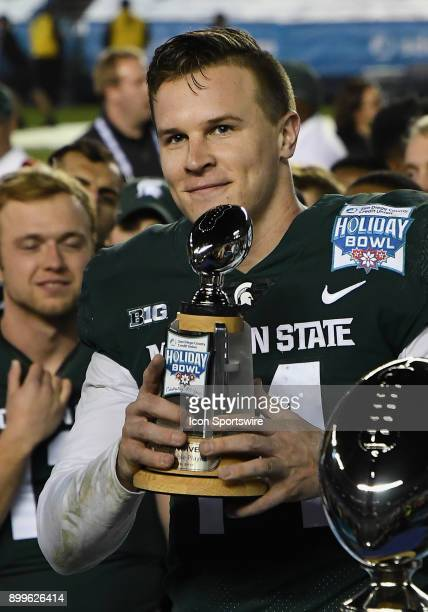 Michigan State Spartans quarterback Brian Lewerke lifts the offensive MVP Trophy on the field after the Spartans defeated the Washington State...