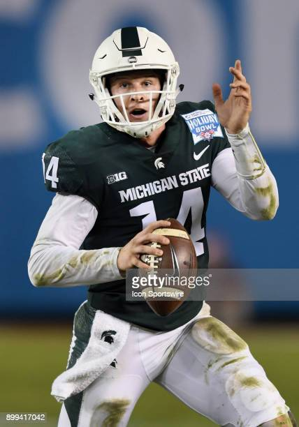 Michigan State Spartans quarterback Brian Lewerke scrambles with the ball in the second quarter of the Holiday Bowl played against the Washington...