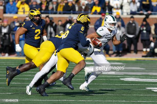 Michigan State Spartans wide receiver Cody White runs with the ball after catching a pass while being pursued by Michigan Wolverines linebacker Josh...